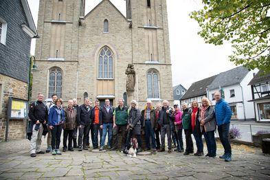 Gruppenfoto von einer Wandergruppe vor einer historischen Kirche. Vor der Menschengruppe sitzt ein Hund.