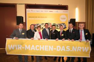 Die Geschäftsführer der nordrhein-westfälischen Eisenbahnverkehrsunternehmen halten ein gelbes Banner hoch, auf dem in weißer Schrift steht: wir-machen-das.nrw