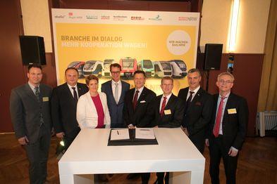 Die Geschäftsführer der nordrhein-westfälischen Eisenbahnverkehrsunternehmen und der NRW-Verkehrsminister Hendrik Wüst stehen hinter einem Tisch, auf dem die unterzeichnete Agenda Bahnen NRW liegt.