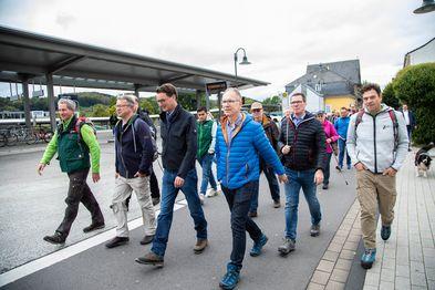 Eine Gruppe von Menschen wandert über das Bahnhofsgelände Overath.
