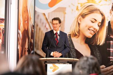 NRW-Verkehrsminister Hendrik Wüst steht an einem Rednerpult vor einem Plakat der App.