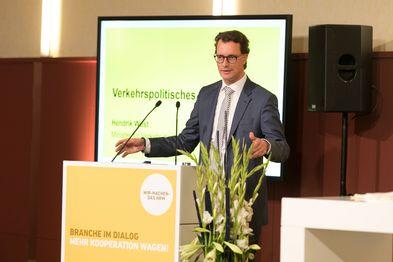 NRW-Verkehrsminister Hendrik Wüst steht bei der Auftaktveranstaltung zur Agenda Bahnen NRW hinter einem Pult und hält eine Rede.