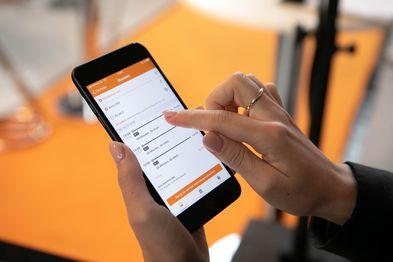 Nahaufnahme eines Handybildschirms, auf dem die mobil.nrw App geöffnet ist. Eine Hand tippt gerade auf dem Bildschirm.