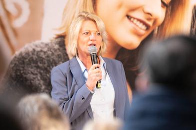 Birgit Strecker vom KCM NRW steht vor einem Plakat der App und spricht in ein Mikrofon.