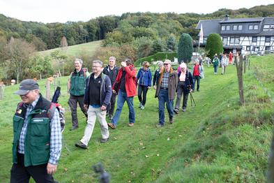 Eine Wandergruppe läuft auf einem Wiesenweg, im Hintergrund ist ein Gasthaus zu sehen.