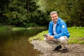 Manuel Andrack hockt mit einem GPS-Gerät an einem kleinen Fluss im Wald.