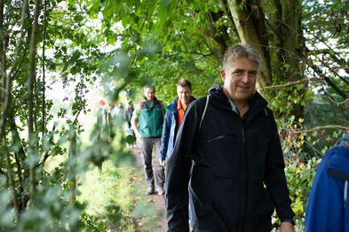 Ein paar Wanderer laufen hintereinander auf einem Waldpfad.