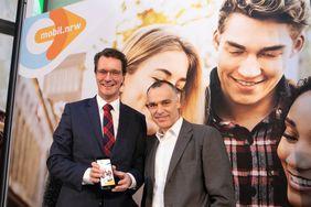 NRW-Verkehrsminister Hendrik Wüst steht neben einem Mann vor einem Plakat der mobil.nrw App und hält ein Smartphone in der Hand, auf dem die App geöffnet ist.