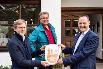 Drei Männer halten die Wanderbahnhof-Plakette 2020 in der Hand.