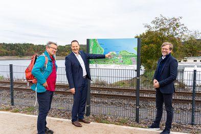 Drei Männer stehen vor einer Hinweistafel an einem See.
