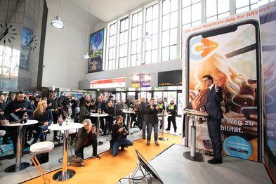 NRW-Verkehrsminister Hendrik Wüst steht an einem Rednerpult, vor ihm stehen viele Pendler und Pressevertreter im Düsseldorfer Hauptbahnhof.