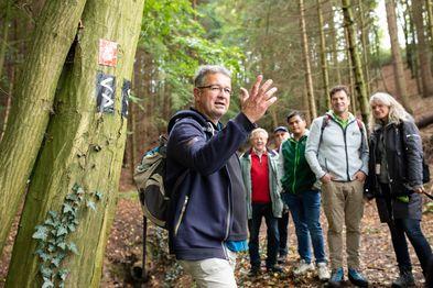 Manuel Andrack steht vor einer Menschengruppe im Wald und erzählt etwas.
