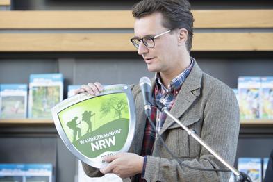 Verkehrsminister Hendrik Wüst übergibt die Plakete.