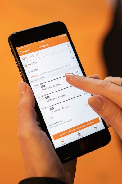 Nahaufnahme der mobil.nrw App auf einem Handybildschirm vor einem orangefarbenen Hintergrund.