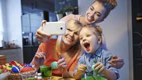 Drei Frauen unterschiedlichen Alters sitzen am Küchentisch und bemalen Ostereier, während sie über ein Handy ein Selfie machen.