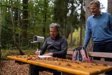 Zwei Männer im Wald, einer sitzt an einem Holztisch und schreibt in ein Buch, der zweite steht hinter ihm und schaut ihm zu.