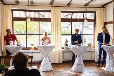 Drei Männer und eine Frau stehen an weißen Stehpulten vor einer Fensterfront.